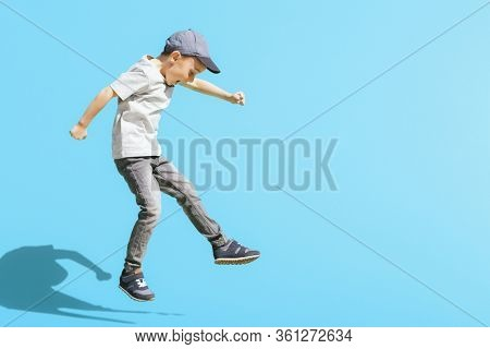 Young boy runs in the jump on the street on a bright blue background