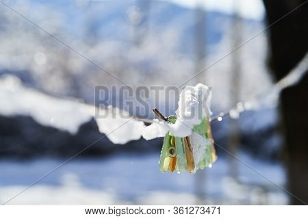 Clothespins On Clothesline Covered With Snow, Close-up, Outdoors.