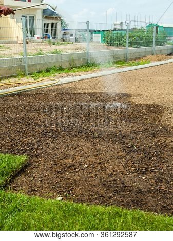 Gardening - Preparing and watering sod for the new lawn