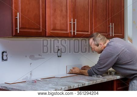 The Working Tile Grouting Applying Grout To The Joint Tiles For Home Improvements To A Kitchen