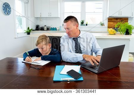 Covid-19 School Lockdowns And Remote Working. Stressed Man Trying To Work From Home With Bored Son