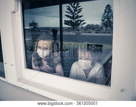 Covid-19 Lockdowns. Sad Children With Face Mask Looking Through The Window During Quarantine At Home