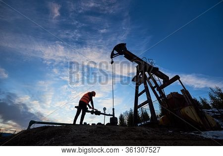 Silhouette Of Oil Man In Work Vest And Helmet. Petroleum Operator Working In Oil Field With Long Str