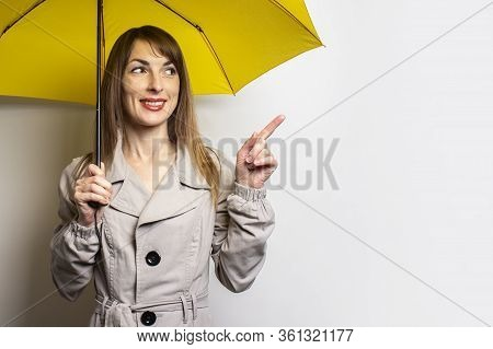Portrait Young Friendly Woman In A Classic Jacket With A Smile Under A Yellow Umbrella Looks Up And