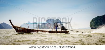 Andaman Sea, Thailand, November 6, 2017: Traditional Thai motor boat is speeding by between the islands in the Andaman Sea