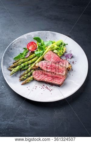 Barbecue dry aged wagyu entrecote beef steak with lettuce and green asparagus as closeup on a modern design plate