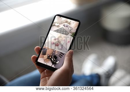 Man Monitoring Modern Cctv Cameras On Smartphone Indoors, Closeup. Home Security System