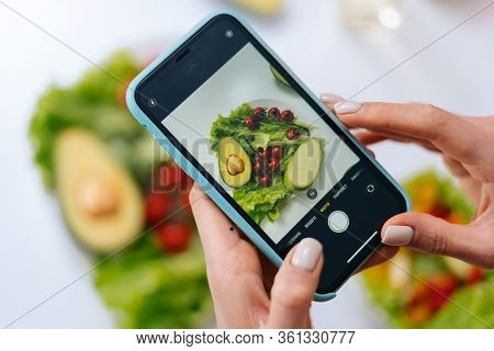 Close-up View Of Woman Making Photos Vegetable Salad With Camera Of Cellphone To Place Pictures At S