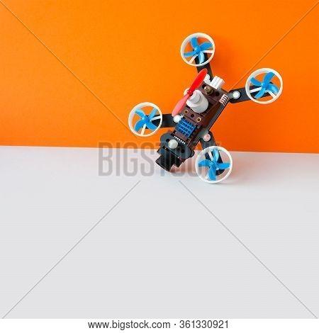 Drone Multicopter With Camera, Orange White Background. Creative Design Aerial Robotic Rotorcraft Me