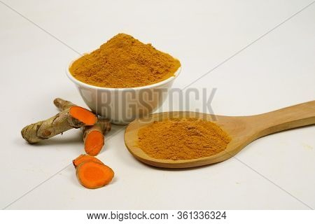 Turmeric Powder In A Wooden Spoon And Turmeric Root Isolated On A White Background, Used As A Tonic