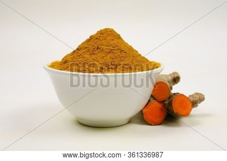 Turmeric Powder In A White Cup And Turmeric Root Isolated On A White Background, Used As A Tonic For