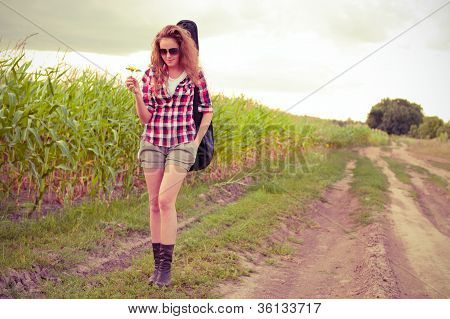 Young Redhead Woman With Guitar Passes Corn Field Outdoors In Summer. Split Toning.