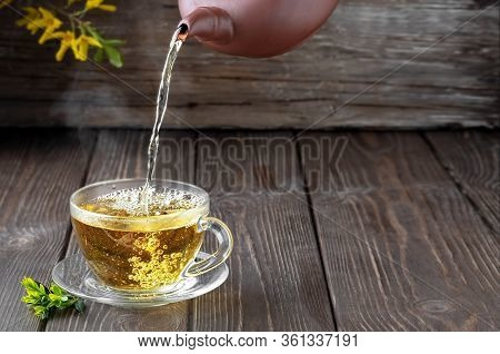 Hot Green Tea Is Poured From The Teapot Into The Glass Bowl, Vintage Wooden Table, Steam Rises Above