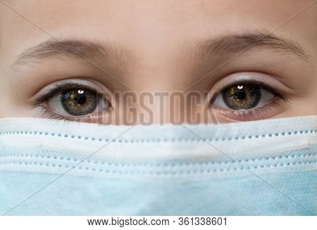 Face Girl With Red Eyes And A Medical Mask On A Black Background, Copy Space. Concept Of People Who