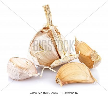 Three Garlic Cloves In The Peel Against Part Of Garlic Head Isolated On White Background With Reflec
