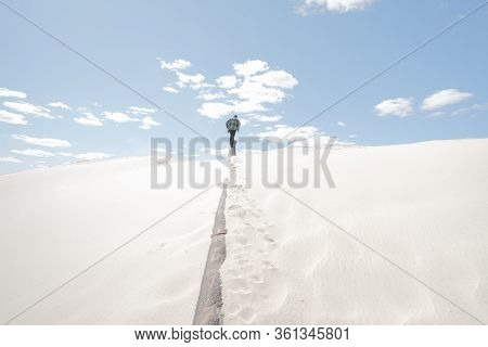 Man Walks Away And Up, Sandy Background. Conceptual Image Panoramic Shot In Sand With Figure Of Male