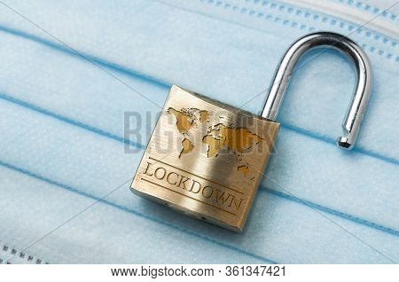 Coronavirus World Lockdown End: An Open Lock With A World Map And The Word Lockdown Engraved On A Li