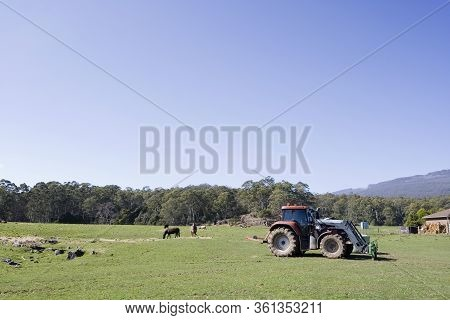 A Rural Landscape In Tasmania With A Tractor On A Farm.