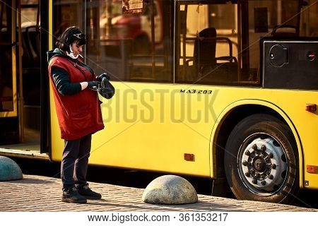 Kyiv, Ukraine, 04.08.2020: The Conductor Is Nervous Smoking Near The Empty Bus And Counting The Mone