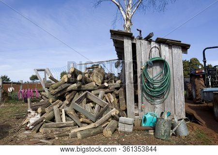 An Old Wooden Shack With A Pile Of Firewood