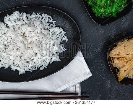 Closeup Of Rice With Soy Asparagus And Chuka On White Napkin On Black Background Top View.