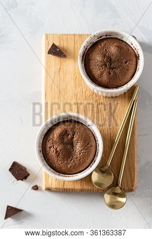 Chocolate Lava Cake With Liquid Centre In Ceramic Molds Ramekins On Wooden Board On White Background