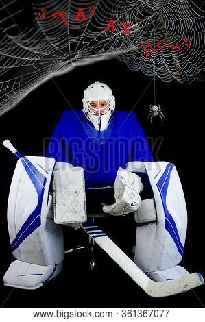 Man In Hockey Goalie Outfit Sitting On Chair. Above Him Are Cobwebs With A Spider. Stay At Home Conc