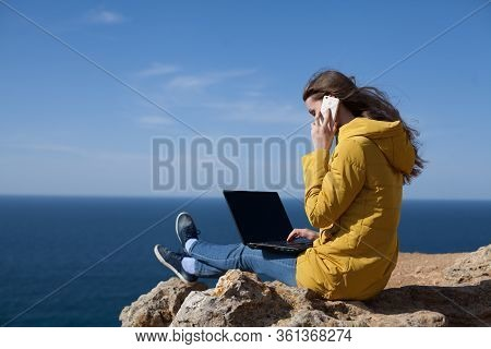 Technology And Travel. Work In The Open Air. The Concept Of Freelancing. A Pretty Young Woman In A Y