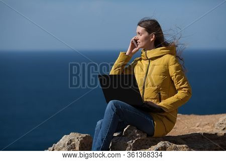 A Freelancer Girl Is Working Typing On A Laptop And Talking On A Mobile Phone With A Beautiful View