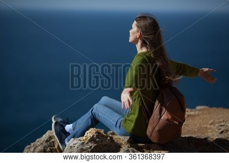 A Beautiful Young Woman Traveler With A Backpack On The Background Of The Sea Opened Her Arms. Copy