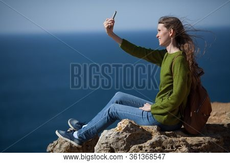 A Young Female Traveler With A Backpack Takes A Selfie On A Smartphone Against The Sea And Smiles. T
