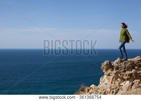 A Young Woman Traveler With A Backpack Is Engaged In Trekking In The Mountains Looking At The Sea. T
