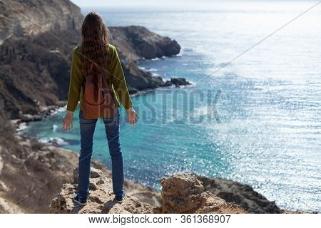 An Attractive Girl With A Backpack On A Trip Looks At The Sea Bay. The Concept Of Travel , Weekends,