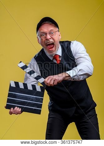Senior Handsome Man Holding A Cinema Clapper. Man Wearing Suit With No Jacket. Person Isolated Again