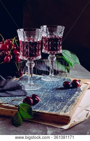 Two Glass With A Red Alcoholic Drink, Old Books And Ripe Cherry Berries On A Black Background. Still