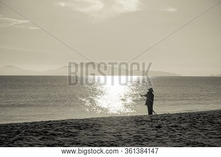 Hoi An, Cua Dai Beach In Vietnam. Silhouette Of A Worker With Typical Conical Hat Cleaning The Sandy