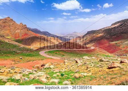Winding Road Through The Mountains. Sunny Day, Blue Sky With Clouds. Colorful Mountain Landscape. Mo