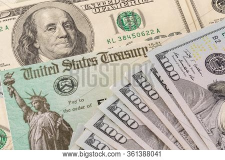 Stack Of 100 Dollar Bills With Illustrative Coronavirus Stimulus Payment Check To Show The Virus Sti