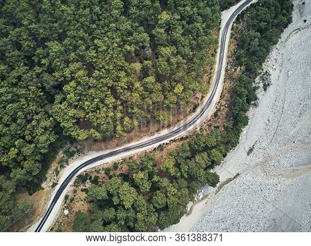 Dry River Bed From Aerial Above. Street Crossing Sideway With Beautiful Green Mediterrain Trees On Y