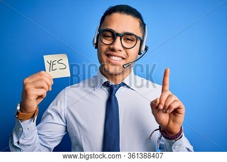 Young brazilian call center agent man holding reminder paper with yes message surprised with an idea or question pointing finger with happy face, number one