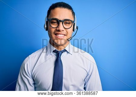 Young brazilian call center agent man wearing glasses and tie working using headset with a happy and cool smile on face. Lucky person.