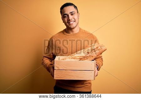 Young baker brazilian man holding box with homemade bread over isolated yellow background with a happy face standing and smiling with a confident smile showing teeth