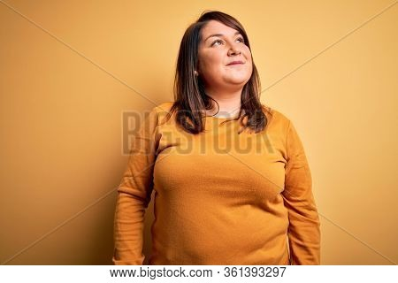 Beautiful brunette plus size woman wearing casual sweater over isolated yellow background smiling looking to the side and staring away thinking.