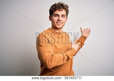 Young blond handsome man with curly hair wearing casual sweater over white background Inviting to enter smiling natural with open hand