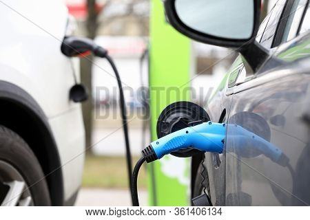 Close-up Of Electric Car Public Charging Station On City Street. Power Supply For Electrocar. Refuel