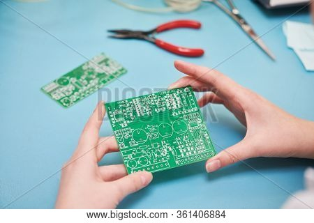 Microcontroller circuit board manufacture. Technician's hand with pcb