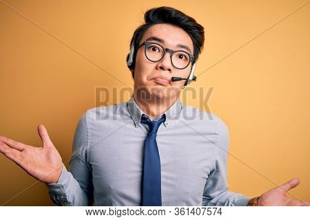 Young handsome chinese call center agent man wering glasses using headset clueless and confused expression with arms and hands raised. Doubt concept.