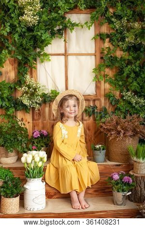 A Little Girl Sits On Porch Of Wooden House, Around Green Houseplants And Flowers. Kid Is In Yellow