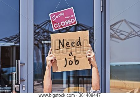 Hands Of Beggar With Sign Looking For A Job Near Closed-door Of Office. Unemployment During Coronavi