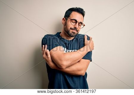 Handsome man with beard wearing t-shirt with volunteer message over white background Hugging oneself happy and positive, smiling confident. Self love and self care